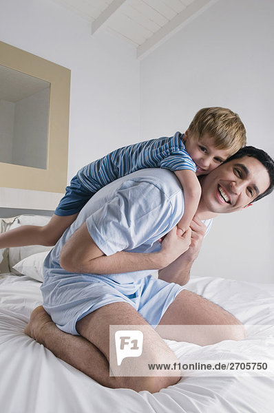 Mid adult man playing with his son on the bed