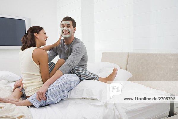 junge Frau junge Frauen eincremen verteilen Mann Gesichtsmaske Maske jung auftragen