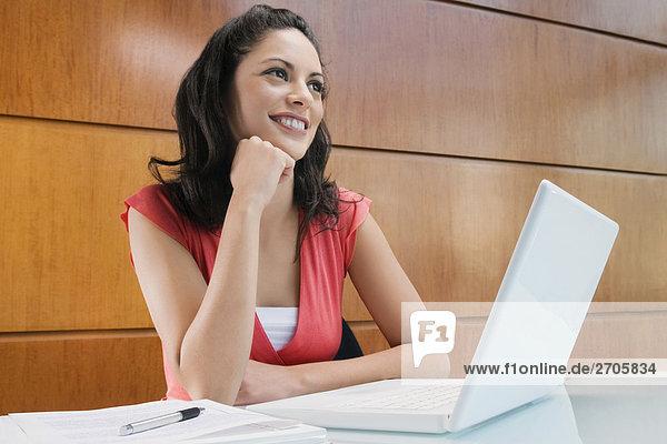 Geschäftsfrau Träumen an einen Laptop lächelnd