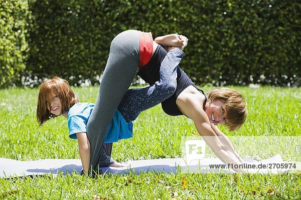 Portrait of a mid adult woman with her daughter practicing yoga