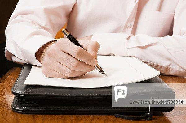 Mitte Schnittansicht eines Kaufmanns Schreiben auf einem Blatt Papier mit einem Stift