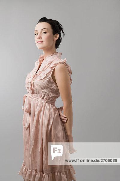 Portrait einer jungen Frau mit ihren Händen hinter ihrem Rücken stehend