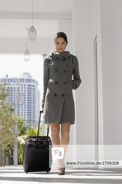 Junge Frau ziehen Gepäck in einem hotel