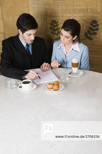 Erhöhte Ansicht eines Kaufmanns und eine geschäftsfrau in einem Café diskutieren