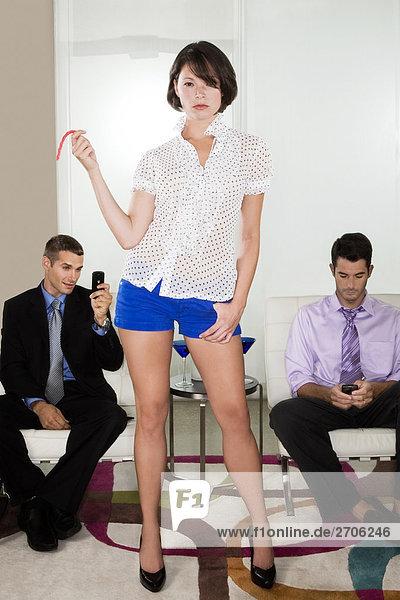 Junge Frau steht vor zwei Männer