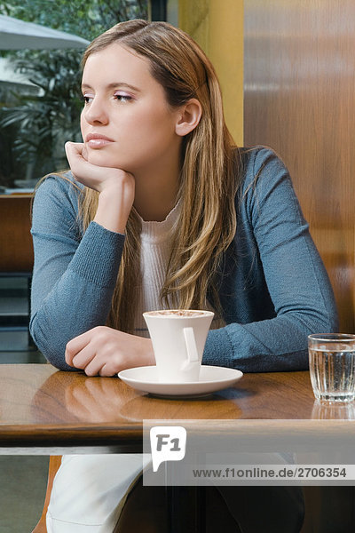 Young woman sitting in a cafe and thinking