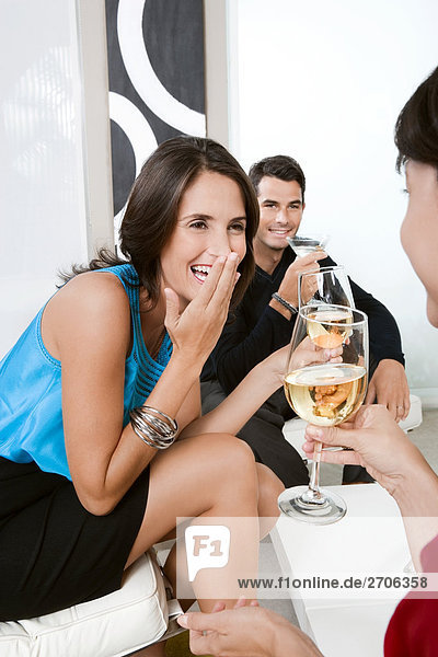 Three friends drinking wine and smiling together