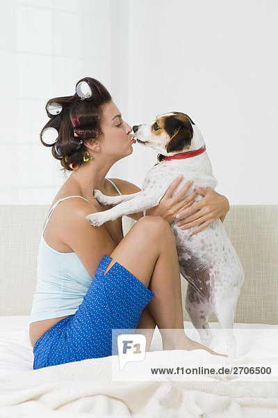 Young woman kissing a puppy on the bed mouth