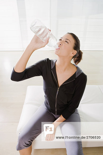 Junge Frau Trinkwasser aus eine Flasche Wasser