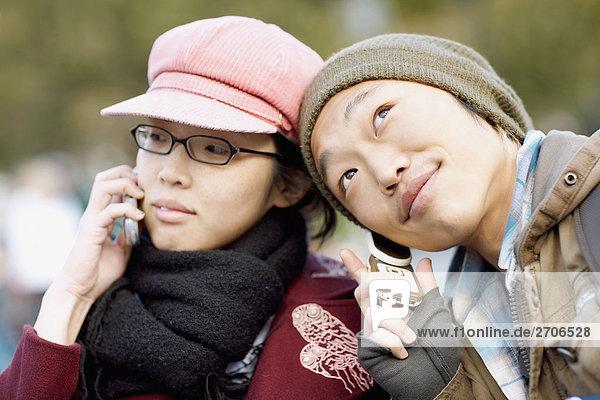 Nahaufnahme der zwei jungen Frauen anhören Mobiltelefone