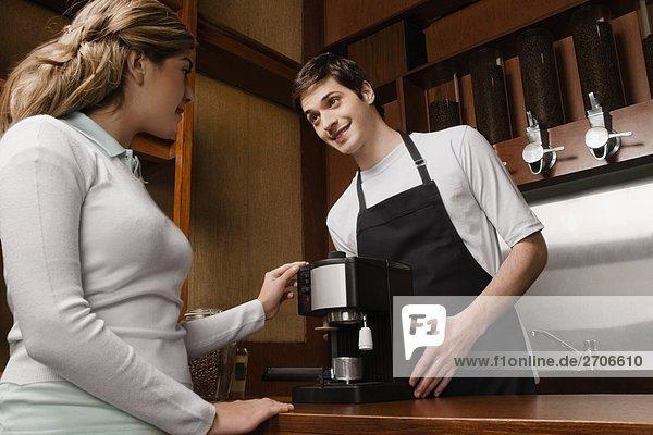 Coffee-Shop-Besitzer  die eine Kaffeemaschine zu einem Kunden