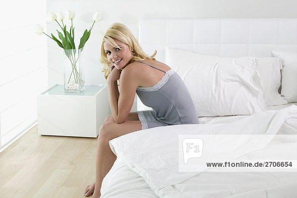 Portrait einer jungen Frau sitzen auf dem Bett und lächelnd
