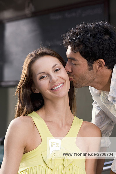 Side profile of a young man kissing a young woman