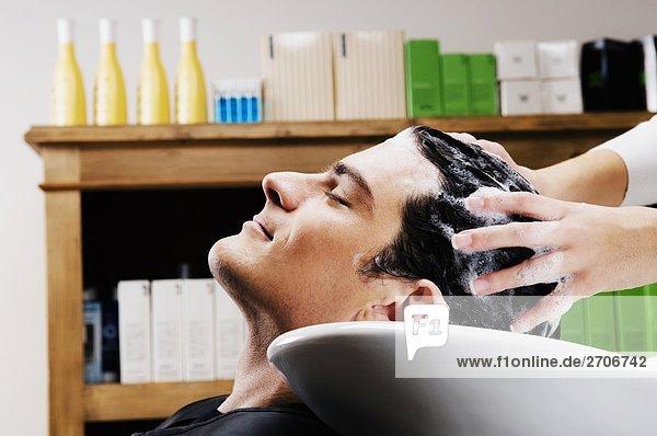 Mitte Erwachsenen Mann sich die Haare shampooniert im salon
