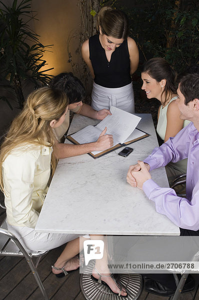 High angle view of two couples looking at a menu in a restaurant