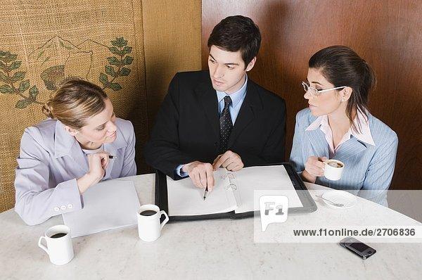 Zwei Unternehmerinnen und Unternehmer in einem Café diskutieren