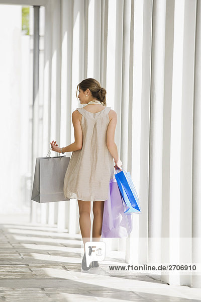 Rear view of a young woman carrying shopping bags