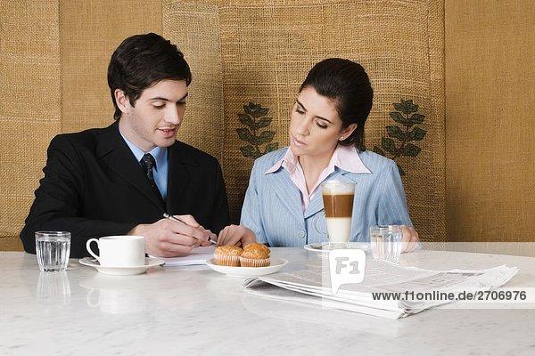 Kaufmann und eine geschäftsfrau in einem Café diskutieren