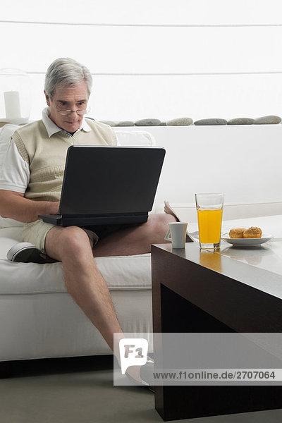 Senior Senioren Mann Notebook arbeiten Tisch Frühstück