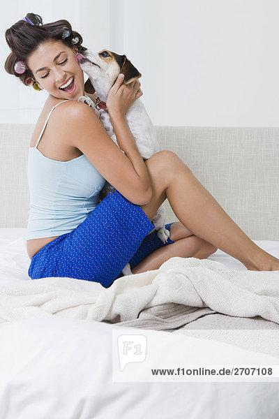 junge Frau junge Frauen halten Bett Welpe