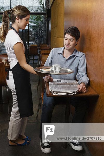Waitress serving Kaffee für einen Kunden