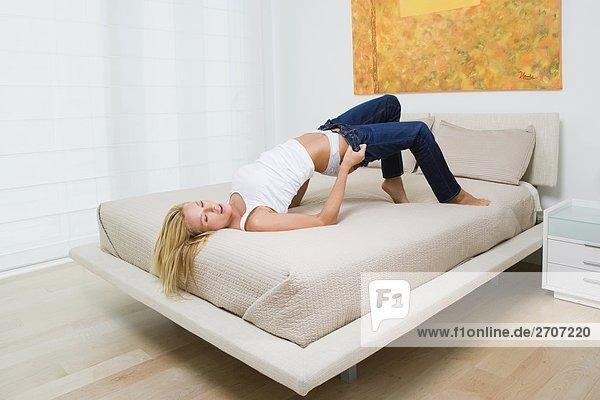 Mitte erwachsen frau auf Jeans auf dem Bett