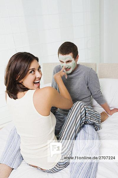 junge Frau junge Frauen eincremen verteilen Portrait Mann Gesichtsmaske Maske jung auftragen