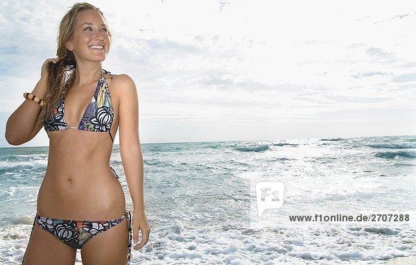 Junge Frau stehen am Strand und lächelnd