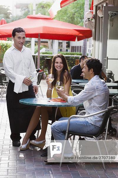 Junges paar in einem Bürgersteig Café mit einem Kellner stehen neben ihnen sitzen