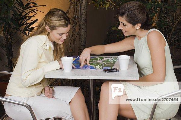 Zwei junge Frauen sitzt in einem Café und lächelnd