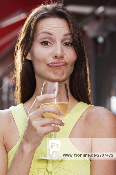 Portrait einer jungen Frau hält ein Glas Wein und Grimasse