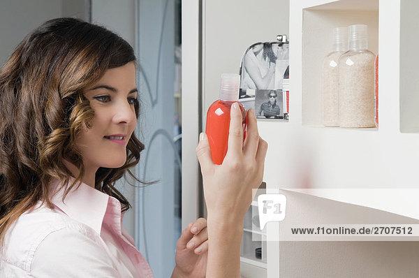 Nahaufnahme of a junge Frau hält eine Flasche Kosmetik