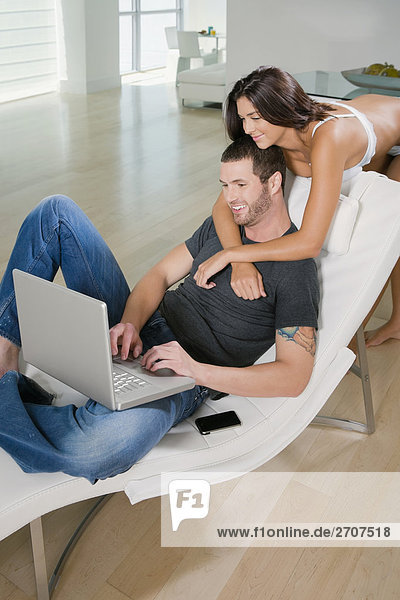 junge Frau junge Frauen benutzen Mann Notebook umarmen lächeln jung