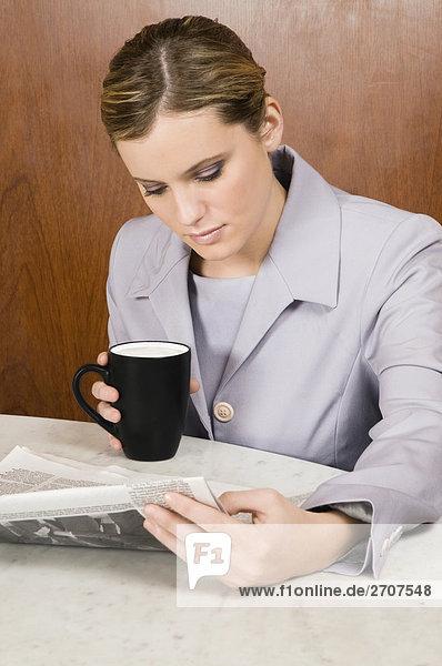 Geschäftsfrau lesen eine Zeitung und halten eine Kaffeetasse