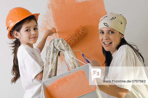 Portrait of a mature woman and her daughter painting a wall