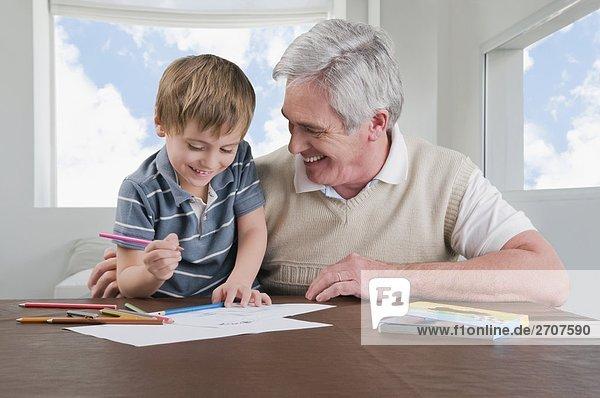 Senior man assisting his grandson in homework
