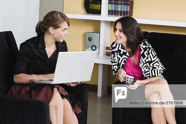 Junge Frau arbeiten auf einem Laptop mit einer Mitte erwachsen frau mit eine Tasse Tee