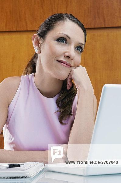 Geschäftsfrau Träumen an einen Laptop mit der Hand auf dem Kinn