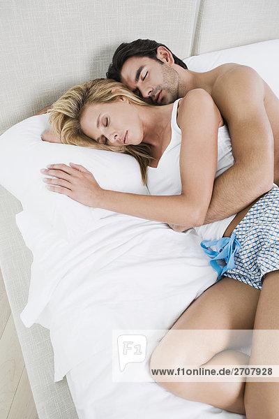 Erhöhte Ansicht eines jungen Mannes und einer Mitte erwachsen frau auf dem Bett liegend