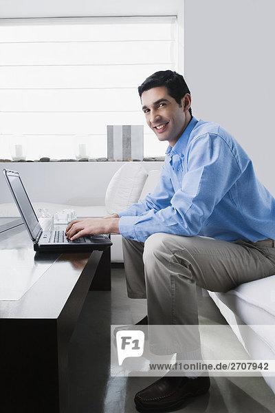 Porträt eines Mitte Erwachsenen Mannes auf einem Laptop arbeiten