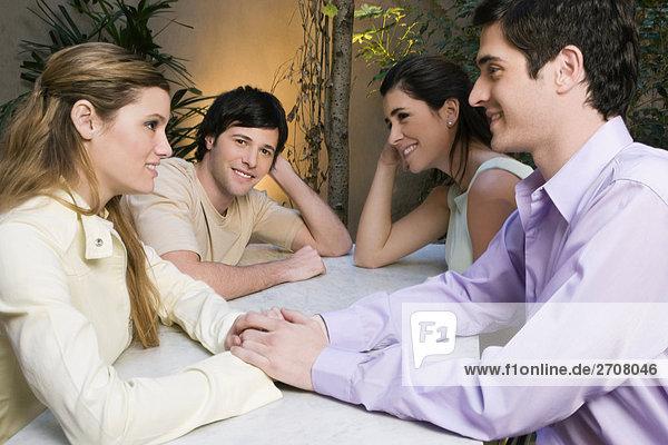 Zwei junge Paare sitzt in einem Café und lächelnd