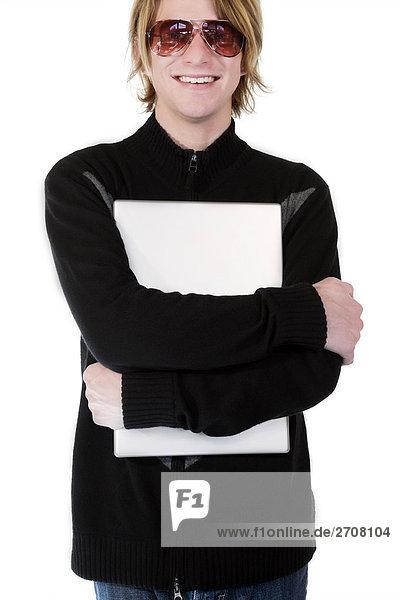 Nahaufnahme eines jungen Mannes umarmt einen Laptop und lächelnd