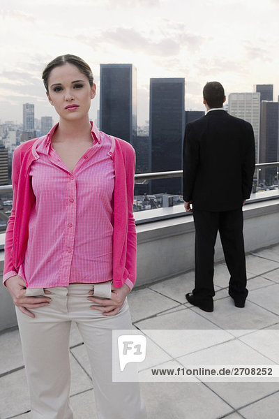 Portrait des ständigen mit Arms akimbo mit einem Geschäftsmann im Hintergrund geschäftsfrau