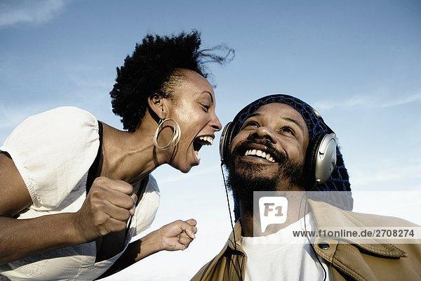 Mitte Erwachsenen Mann hören Musik und eine junge Frau schreien vor