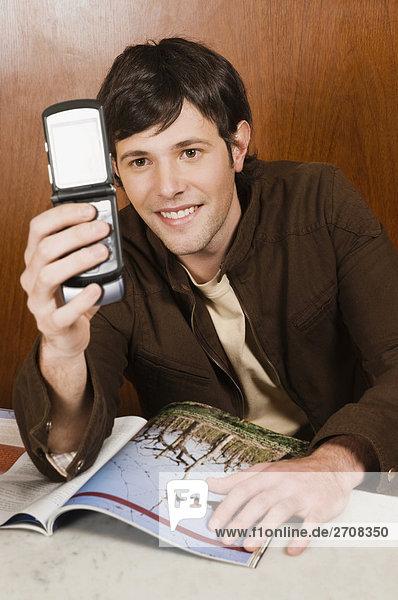 Junger Mann hält ein bewegliches Telefon in einem Café und lächelnd