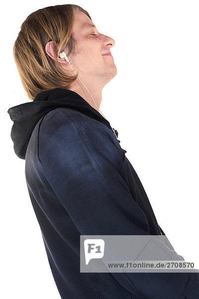 Seitenprofil ein junger Mann Musikhören mit Ohrhörer und lächelnd