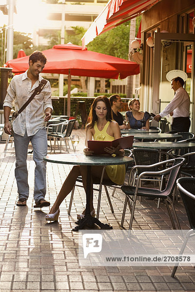 Junge Frau Blick auf ein Menü mit einer jungen Frau lächelnd in einem Bürgersteig Café