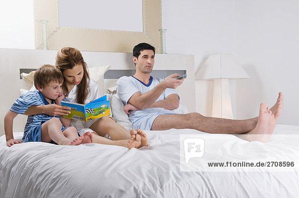 Mann mittleren Alters zuguckend GLOTZE neben seiner Frau und Sohn auf dem Bett