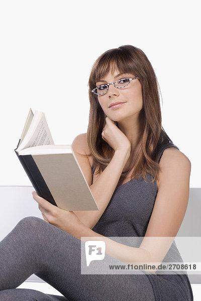 Portrait einer jungen Frau die ein Buch liest