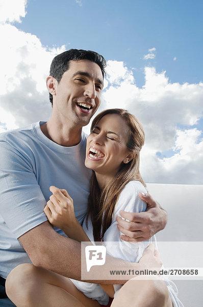Mitte erwachsenen Menschen umarmen eine Mitte Erwachsene Frau und lächelnd